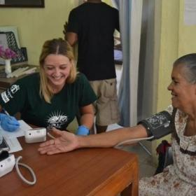 During outreach work in Sri Lanka, a public health intern takes a woman's blood pressure reading.